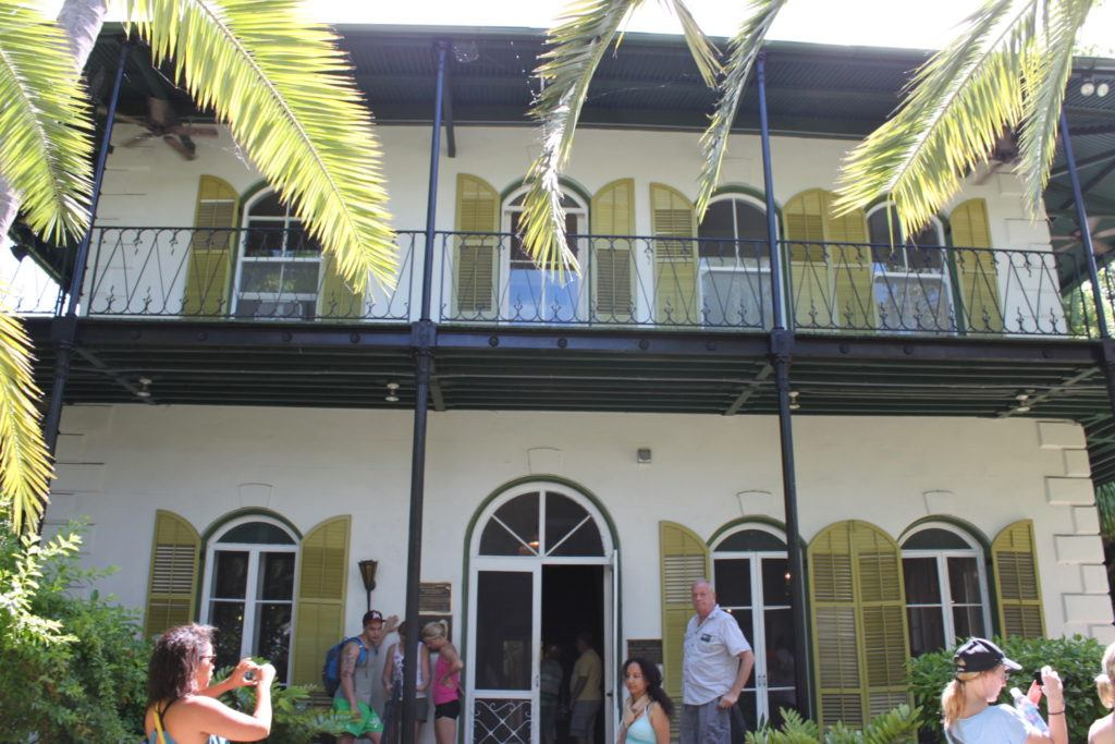 A white stone building with a metal upper porch and green shutters flanked by palm trees at  Ernest Hemingway Home & Museum in Key West